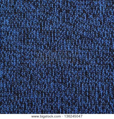Fragment of a black and blue sweater's cloth fabric material texture as an abstract background composition