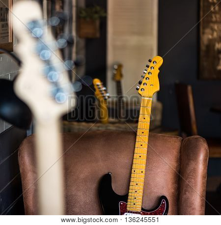 Detail of Electric Guitar Neck Leaning Against Leather Seat. Other Necks in Background and Foreground.