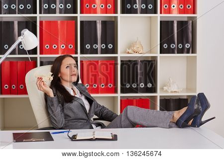 Businesswoman with a  model of plane sits on a workplace in the office.