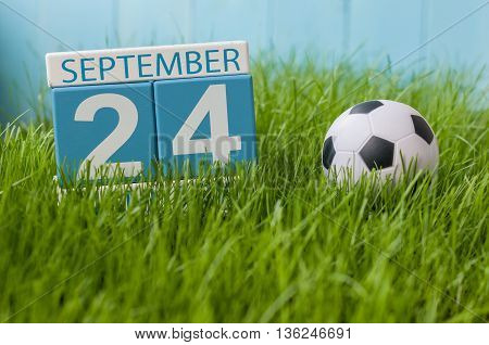 September 24th. Image of september 24 wooden color calendar on green grass lawn background. Autumn day. Empty space for text.