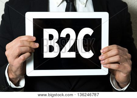 Business man holding a tablet with the text: B2C