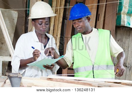 The  carpenter dictate to his trainee what she must write