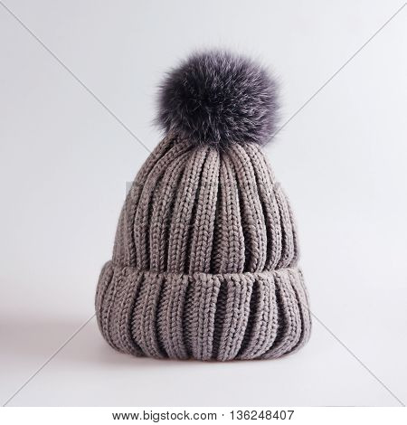 Knitted hat with bubo in grey background