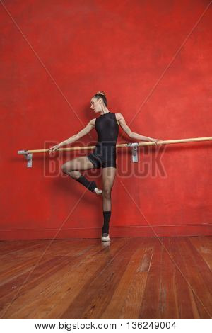 Female Ballet Dancer Practicing At Bar In Studio