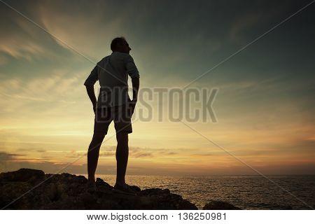 Man on the sea coast look on the sunset