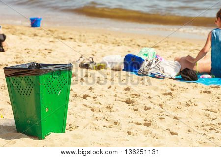 Order and cleanliness at the beach. Tourists resting lying on seaside. Green metal trash can on sand.
