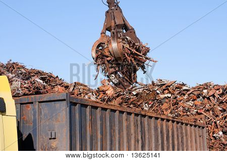 Crane Grabber Loading A Truck With Metal Scrap