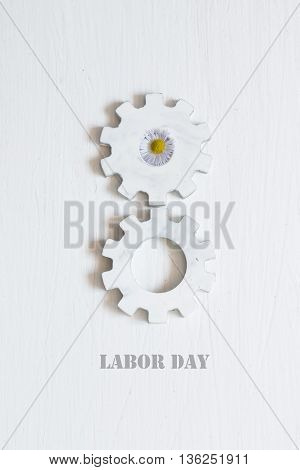 Labor Day inscription and white gears on the white background