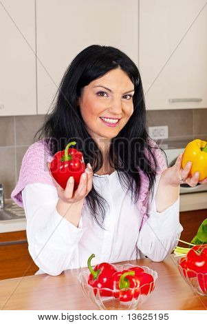 Smiling Woman Holding Red And Yellow Peppers