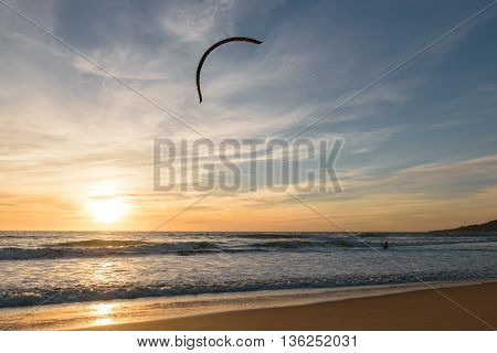 A Kitesurfer going into the Atlantic Ocean at a colorful sunset with his Kite high up in the air in Tarifa, Spain.
