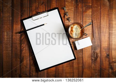 Blank paperwork template for designers. Responsive design mockup on vintage wooden background. Blank paper letterhead coffee cup business cards and pencil on wooden table background. Top view.
