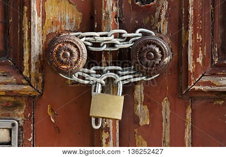 Old grungy wooden door with peeling paint and round door-handles with chain