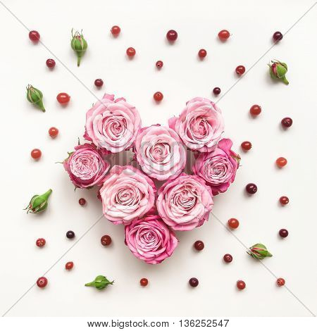 Heart symbol made of bright roses berries and leaves on white background. Flat lay