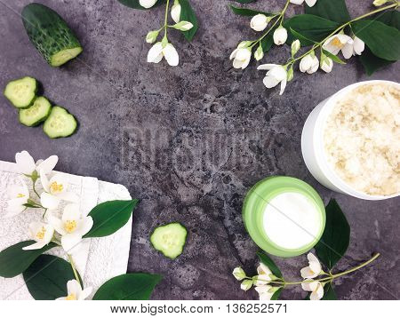 Set of spa treatment products and jasmine flowers on stone background. Flat lay