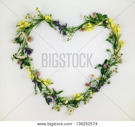 Heart symbol made of meadow flowers and leaves on white background. Flat lay top view