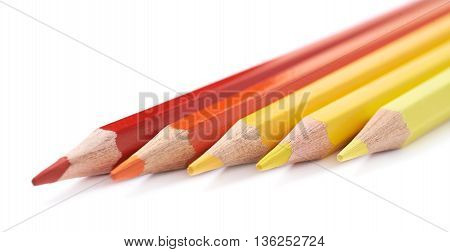 Line of five color pencils, composition isolated over the white background, close-up crop fragment composition