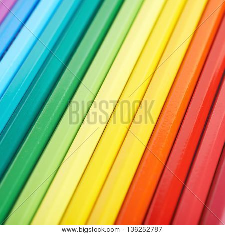 Multiple colorful color pencils composition arranged in a line to form a rainbow gradient, close-up crop fragment