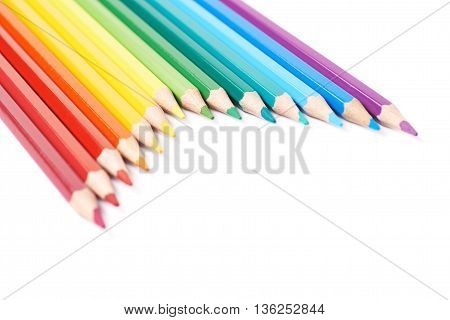 Multiple colorful color pencils composition arranged in a line to form a rainbow gradient, composition isolated over the white background