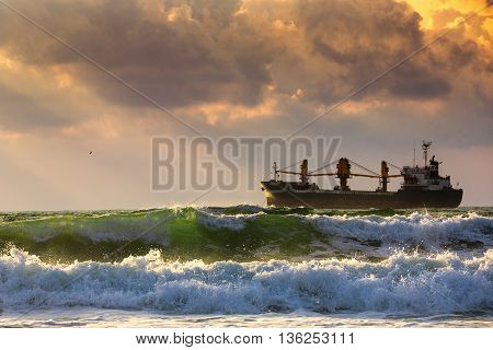Sun setting at the sea with sailing cargo ship scenic view