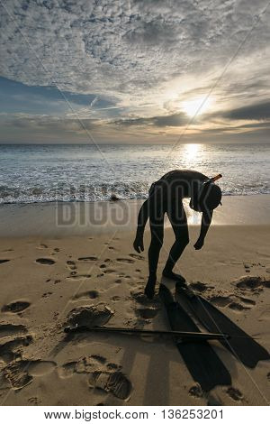 A snorkeler with a harpoon standing on a beach at sunset and clouds in the sky in Tarifa, Spain-