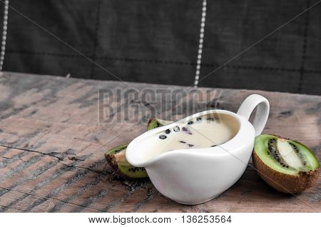 Yogurt with strawberry slices and blueberries on a wooden board - near the yogurt lie kiwi slices