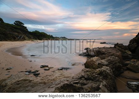 Landscape of a beach at the Costa de la Luz in Tarifa, Spain with a wooden stair as the entry to the beach. Photo taken at a colorful sunset, rocks in the foreground, Morocco in the background.