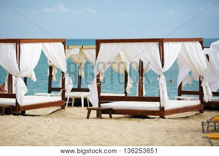 White beach canopies. Luxury beach tents at the resort for relaxation and spa treatments.