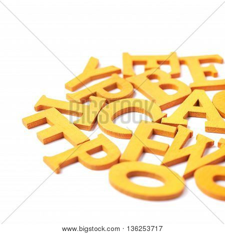 White surface covered with the multiple colorful orange painted wooden letters as a backdrop composition in yellow