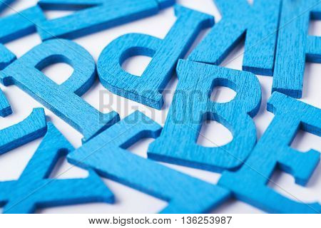 White surface covered with the multiple colorful painted wooden letters as a backdrop composition in blue
