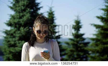 young woman uses the app on your phone or typing SMS outdoors.