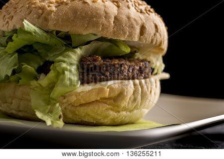 Detail of veggie burger with rissoles and fresh lettuce. Over black background.