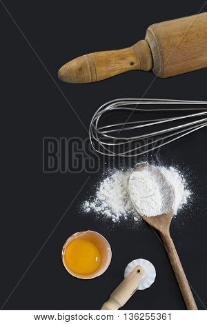 Rolling pin, whisk, flour and eggs on black background