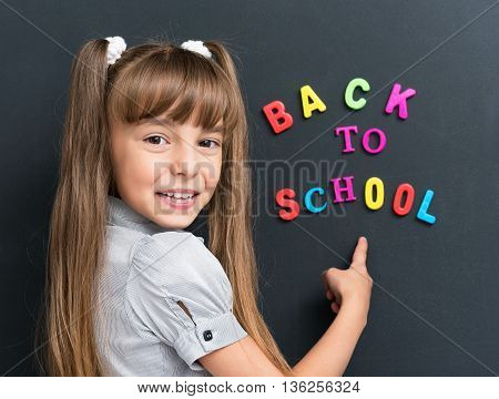 Schoolgirl posing at the black chalkboard in classroom. Back to school concept.