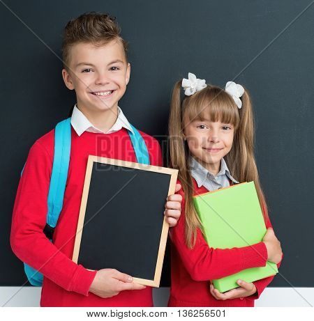Happy pupils posing together in front of a big chalkboard