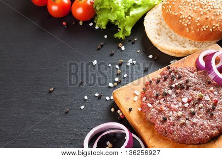 The raw ingredients for the homemade burger on black slate background.