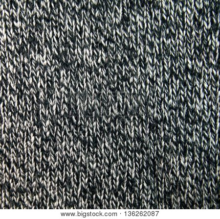 Black and white knitted fabric. With close interlacing yarns home rustic knitting. Background