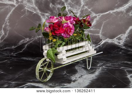 A wheelbarrow full of roses against a marble background