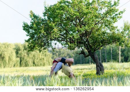 Young couple training in acro yoga in the park