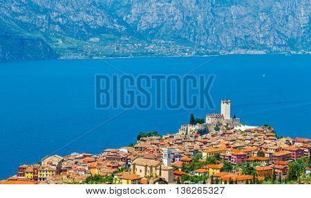 Top view to ancient tower and fortress in old town malcesine at garda lake veneto region italy mountains on background summer landscape with colorful houses roofs green trees