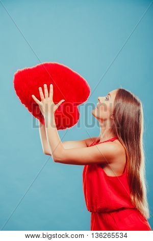 Pretty cute young woman girl throwing red heart shape pillow in studio on blue. Valentines day love.