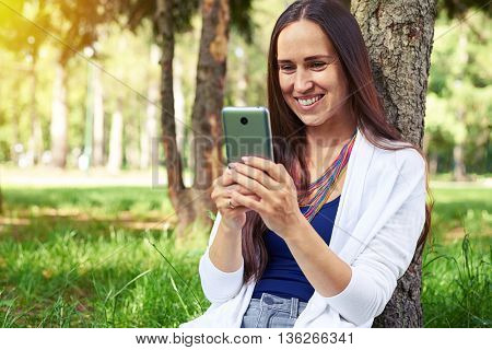 Smiling beautiful woman is sitting under tree in picturesque park and using her smart phone