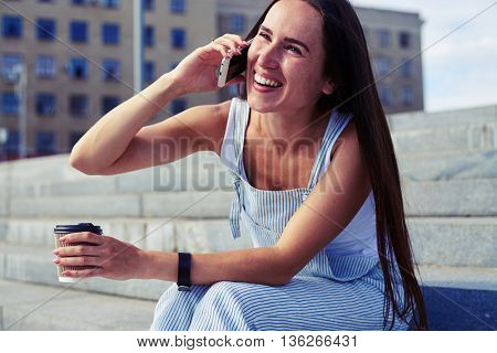 Attractive young woman in casual clothes is talking on the phone and laughing while sitting on stairs in the street with a cup of coffee