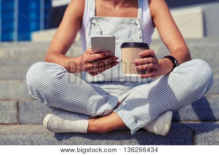 Close-up of slim woman sitting with crossed legs and holding a cup of coffee in one hand and smart phone in another
