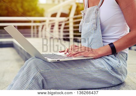 Close-up of young woman in casual clothes working outdoors on her laptop on fresh air under mild morning sun