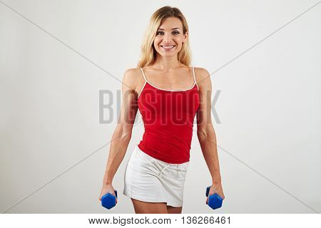 Attractive woman with well trained body is standing with dumbbells in her hands on white background
