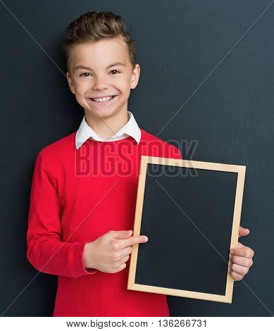 Happy pupil - teen boy posing with small blackboard in front of a big chalkboard. Back to school concept.