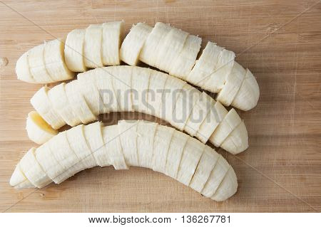 pulled and sliced banana on wood background
