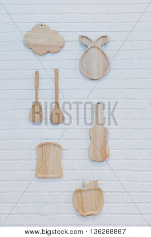 wooden chopping block in cloud bread apple guitar pear shape with wooden spoon and fork hang on white cement wall in dinning room or kitchen