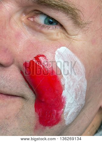 Closeup of young Polish supporter face painted with national flag colors
