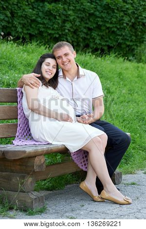 pregnant woman and husband on outdoor, happy family, couple in city park, summer season, green grass and trees